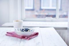 Talerz z muesli i jagody, kawa w filiżance dla śniadaniowej pieluchy w czerwonej klatce na białym drewnianym stole okno bezpłatny Zdjęcie Royalty Free
