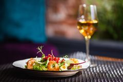 Talerz z piękną apetyczną sałatką świezi warzywa, garnele, przepiórek jajka i lingonberries, jest na stole z napojem Obrazy Stock