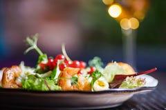 Talerz z piękną apetyczną sałatką świezi warzywa, garnele, przepiórek jajka i lingonberries, jest na stole z napojem Zdjęcie Royalty Free