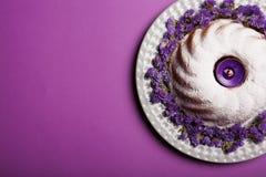 Talerz z round tortem kropiącym z sproszkowanym cukierem i świeczką w centrum na jaskrawym fiołkowym tle, odgórny widok Zdjęcie Stock