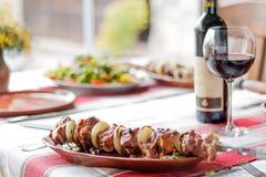 Talerz z shish kebabem i wino na stole Zdjęcia Stock