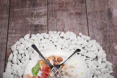 Talerz z solonym mięsem, ser, orzechy włoscy, basil, lud i nóż na bielu kamieniach na drewnianym tle i, obrazy royalty free