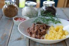 Talerz z stewed spirala makaronem na wieśniaka stole i mięsem zdjęcie royalty free