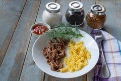 Talerz z stewed spirala makaronem na wieśniaka stole i mięsem obrazy stock