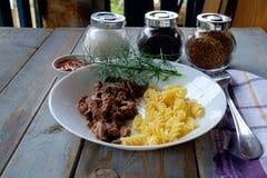 Talerz z stewed spirala makaronem na wieśniaka stole i mięsem fotografia stock