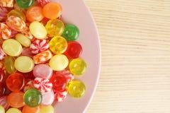Talerz z wyśmienicie kolorowymi cukierkami na drewnianym stole zdjęcia royalty free