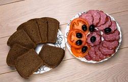 Talerze pokrojony czarny chleb i kiełbasa na drewnianym stole fotografia royalty free