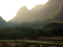 Tales of the riverbank Laos. Sun setting through the jungle covered mountains in northern laos stock image