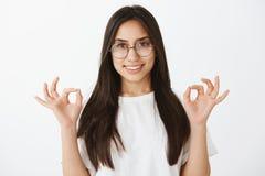 Talia strzał kreatywnie piękna europejska kobieta z garbnikującą skórą w modnym eyewear, podnoszący ręki w zen lub ok zdjęcia stock