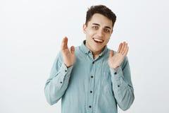Talia strzał spina ręki w aplauzie i ono uśmiecha się szeroko zadowolony atrakcyjny samiec model w turkusowej koszula, fotografia stock