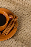Talian espresso on burlap. Closeup shot of freshly prepared cup of italian espresso with cinnamon, coffe beans, nuts and lemon over sacking Royalty Free Stock Images
