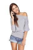 Taling fêmea de sorriso em seu móbil Fotografia de Stock Royalty Free