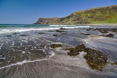 Talisker Bay, Isle of Skye, Scotland - Sandy beach with seaweed in the foreground and white surf and sea cliffs in the distance Royalty Free Stock Image