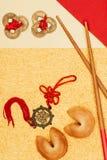 Talismani cinesi con i biscotti di fortuna ed i bastoncini su superficie dorata, concetto cinese del nuovo anno Immagine Stock Libera da Diritti
