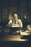 50-taljournalist i hans kontor sent på natten Royaltyfri Foto