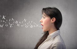 Talk. Young woman talking with alphabet letters coming out of her mouth Stock Image