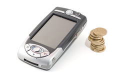 Talk ain't cheap. PDA Mobile Phone with pile of coins, on white, with clipping path Stock Photos