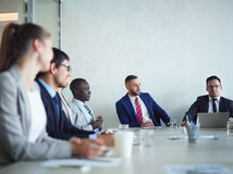 Talk at briefing. Group of people in formalwear having discussion of modern business at meeting stock image