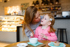 Talk in cafeteria. Daughter and mother talking in cafeteria by dessert royalty free stock images