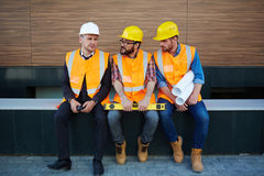Talk of constructors. Three inspectors in uniforms amd helmets discussing new project Royalty Free Stock Images