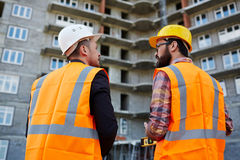 Talk of contractors. Backs of two builders in uniform having discussion on background of unfinished edifice Stock Image