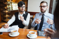 Talk of entrepreneurs. Contemporary entrepreneurs having business discussion in cafe Royalty Free Stock Image