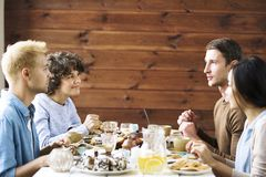 Talk by festive table. Young friendly people sitting by festive table, having talk by dessert and relaxing Stock Images