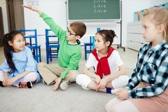 Talk on the floor. Cute schoolboy explaining something to his classmates while talking on the floor of classroom royalty free stock image