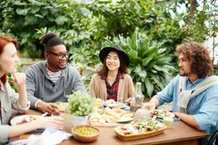 Talk of friends. Group of young intercultural friends having talk by served table at breakfast Royalty Free Stock Photos