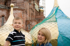 Talk about God. Young mother and son to build a new temple of God. In the background the new golden cupola and the temple stock images