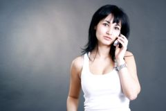 A talk on the phone. Young woman talking on the phone looking serious royalty free stock photo
