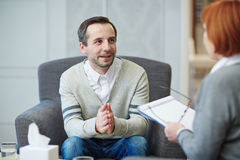 Talk with psychologist. Happy men looking at his psychologist during conversation royalty free stock images