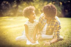 Talk about school. African American father and daughter writing together in nature royalty free stock photos