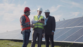 Talk about solar power. Three mixed race men standing in solar power station and discussing something using digital tablet for visualization Royalty Free Stock Photography