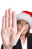 Talk to the Hand. Older senior business woman's arthritic hand with knobbly fingers in a stop talk to the hand gesture. Wearing a santa hat Stock Image
