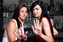 Talk to the hand. Two women at a bar refusing unwanted advances Stock Photos
