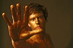 Talk to the hand. Abstract portrait male with hand extended out . he's out of focus and painted gold Stock Photography