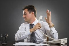 Talk to the hand!. Annoyed indifferent businessman having an uninteresting phone conversation while holding receiver facing the other hand palm in a talk-to-the Royalty Free Stock Photos