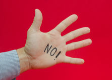 Talk to the hand or saying no to something suggested by a busine. Ss man's hand with no writen on it on a red alerted background Stock Image