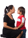 Talk to me. Young mother with dark hair in a black dress talking with his son Royalty Free Stock Photo
