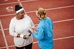 Talk with trainer. Young plump female listening to her instructor speaking about progress in sport Stock Photography