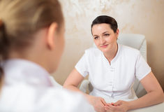 Talk of two female cosmeticians in the office room Stock Photography