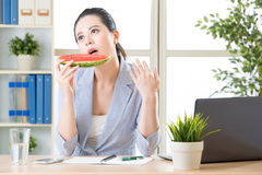 Talk about your investment portfolio after I finish watermelon. Too hot to talk about your investment portfolio after I finish watermelon Royalty Free Stock Image