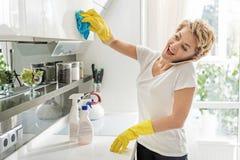 Talkative cheerful woman wiping cupboard Royalty Free Stock Photos