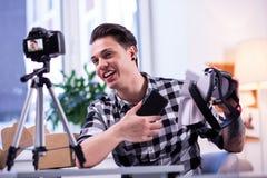 Talkative good-looking man in checkered shirt explaining characteristics. Virtual reality gadget. Talkative good-looking man in checkered shirt explaining stock images