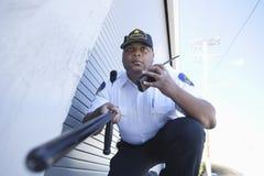Talkie van veiligheidsagentinvestigates with walkie Stock Afbeeldingen