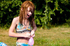 Talking. A girl ties a water balloon closed royalty free stock image