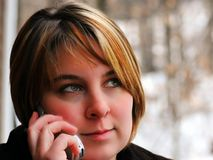 Talking. A woman is outside in the snow covered landscape talking on a mobile phone Stock Photo