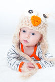 Talking Baby Wearing Owl Costume Hat. Baby lying on his stomach wearing warm clothes and owl hat Stock Photography