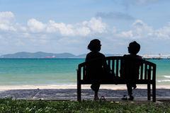 Talking on the beach. Tow women are talking on bench at the beach Royalty Free Stock Image